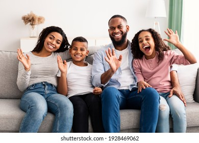 Happy Loving Family. Portrait of cheerful African American man, woman, boy and girl sitting on the sofa at home, posing for photo and waving hands to camera. Four smiling young black people