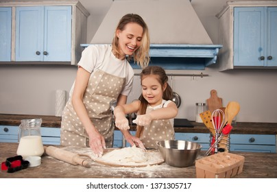 happy loving family is preparing bakery together. Mother and child daughter girl are making cookies and having fun in the kitchen. Mother teaches her daughter to knead the dough at the kitchen table
