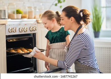 Happy loving family are preparing bakery together. Mother and child daughter girl are cooking cookies and having fun in the kitchen. Homemade food and little helper.   - Shutterstock ID 1687741267