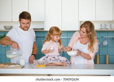 Happy loving family are preparing bakery together. Father pouring milk
