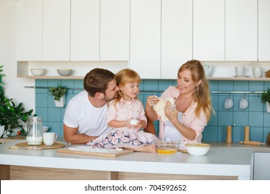 Happy loving family are preparing bakery together. Mother, father and child daughter girl are cooking cookies and having fun in the kitchen. Homemade food and little helper