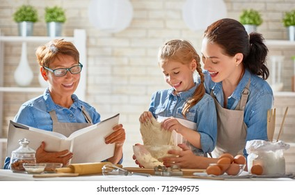 Happy loving family are preparing bakery together. Granny, mom and child daughter girl are cooking cookies and having fun in the kitchen. Homemade food and little helper.