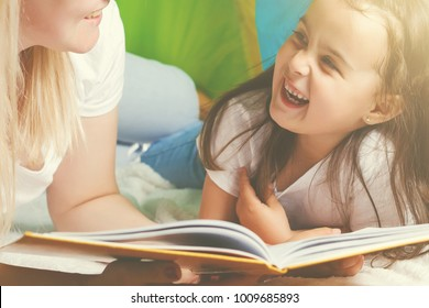 Happy loving family. Pretty young mother reading a book to her daughter tent, indoors