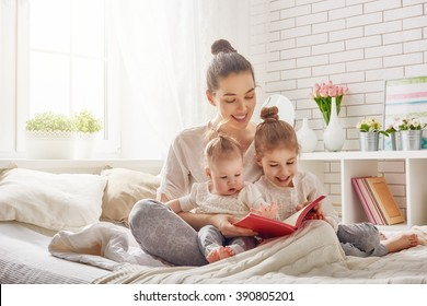 happy loving family. pretty young mother reading a book to her daughters