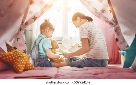 Happy loving family. Pretty young mother reading a book to her daughter indoors. Funny mom and lovely child having fun in children room.