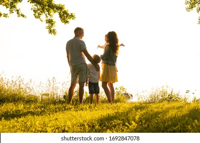 Happy loving family walking outdoor in the light of sunset. Father, mother, son and daughter.