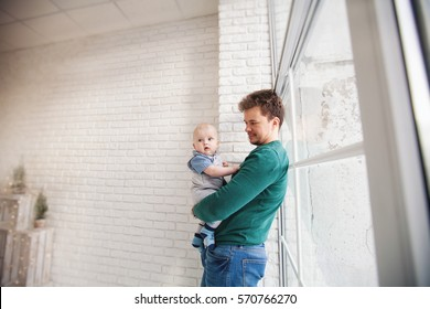 Happy loving family. Young father holds baby son in her arms.