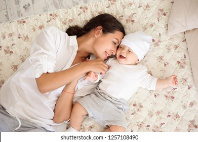 Happy loving family. Young mother are playing with her baby boy in the bedroom. Mom and child are having fun.