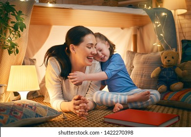 Happy loving family. Young mother and her daughter girl playing in kids room at the bedtime. Funny mom and lovely child are having fun with tent indoors.