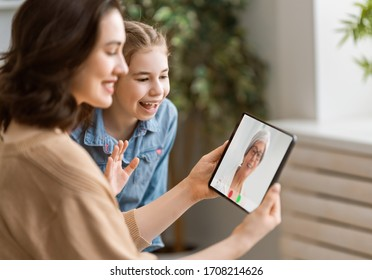 Happy loving family. Young mother and daughter girl using tablet pc for remote conversation with grandma. Funny mom and lovely child are having fun staying at home.