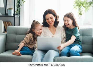 행복한 사랑스런 가족어린 어머니와 딸들이 노트북을 사용합니다.재미있는 엄마와 사랑스러운 아이들이 집에서 즐겁게 지내고 있어요.