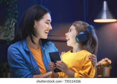 Happy loving family. Young mother and her daughter girl are playing in bedroom. Funny mom and lovely child are having fun with phone.