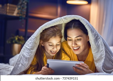 Happy loving family. Young mother and her daughter girl are playing in bedroom. Funny mom and lovely child are having fun with tablet.