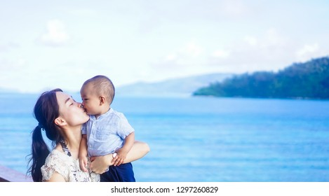 Happy loving family.Asian mother and baby boy playing, kissing and hugging on the sea and island background in summer.