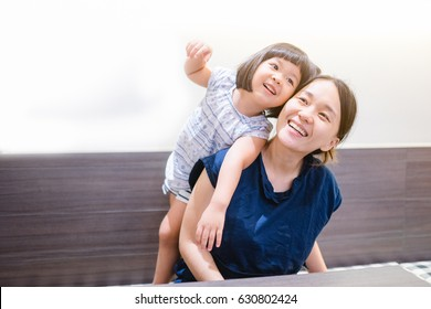 Happy loving family.Asian mother and child girl playing, kissing and hugging