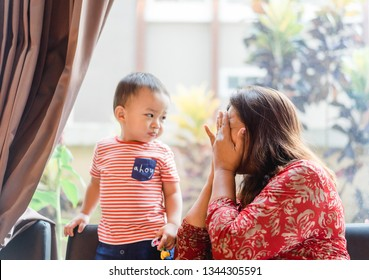 Happy loving family.Grandmother and grandson are having a good time together and playing peekaboo or peek-a-boo at home.Grandson is smiling and laughing with his grandmother.