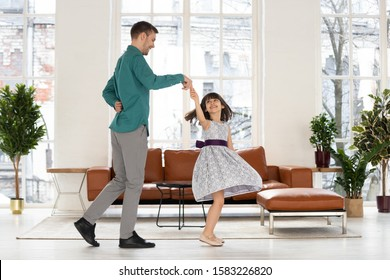 Happy loving father holding hand of adorable daughter dancing to favorite song at home. Smiling dad teaching his young girl and twisting cute little kid. Having fun together in living room.