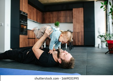 Happy loving father lying on a floor of an apartment, lifting his baby in the air. Smiling, laughing.