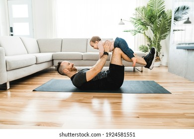 Happy loving father lying on a floor of an apartment, lifting his baby in the air. Smiling. Baby looks at someone.