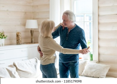 Happy loving mature senior couple dancing at home in living room, smiling middle aged husband and wife having fun in new beautiful wooden house, old family relaxing together enjoy weekend lifestyle