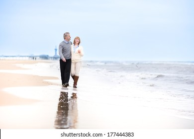 Happy loving middle aged couple walking on a beautiful beach in Holland