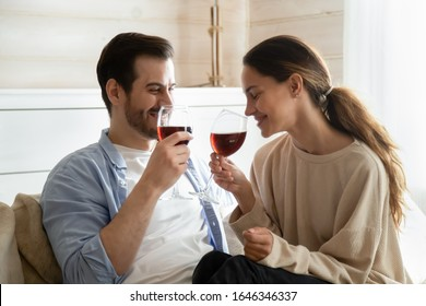 Happy loving millennial couple sit relax on couch in living room drinking red wine enjoying romantic weekend at home, smiling young man and woman spend leisure day cuddle on domestic date