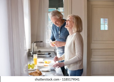 Happy loving senior couple having fun preparing healthy food on breakfast in the kitchen, mature smiling man and woman laughing cooking together on weekend morning, aged old family at home concept