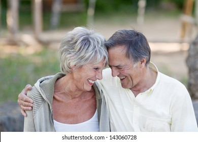 Happy loving senior couple with head to head smiling in park
