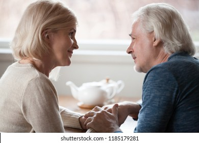 Happy loving senior middle aged retired family couple holding hands looking in the eyes giving care psychological support to older, understanding in good relations, trust devotion in marriage concept