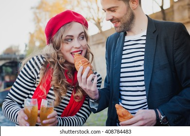 Happy loving stereotypical french couple  eating croissants and drinking champagne near the River Seine