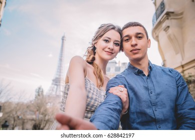 Happy loving stereotypical french couple making selfie on a date under the Eiffel Tower in Paris, France.