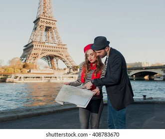 Happy loving stereotypical french tourist couple Looking At Map and searching the direction under the Eiffel Tower in Paris, France