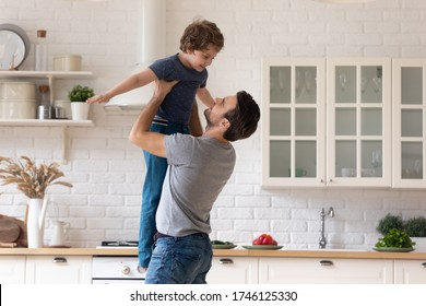 Happy loving young dad hug lift in air play in kitchen with little preschooler son, overjoyed father have fun engaged in playful activity or game with small boy child at home, entertainment concept