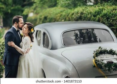 Happy luxury wedding couple kissing and embracing near retro car.