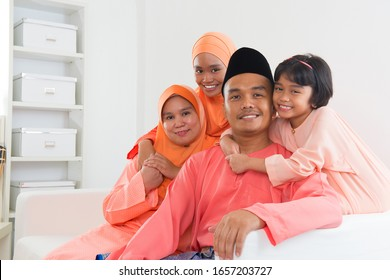 Happy Malay family portrait in traditional clothing during Hari Raya. Malaysian family lifestyle at home.