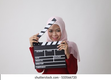 happy malay with red tudung holding clapper board smiling