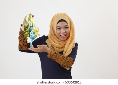 happy malay woman holding a bunch of decorative ketupat