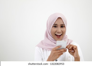 happy malay woman with tudung using smart phone on the white background