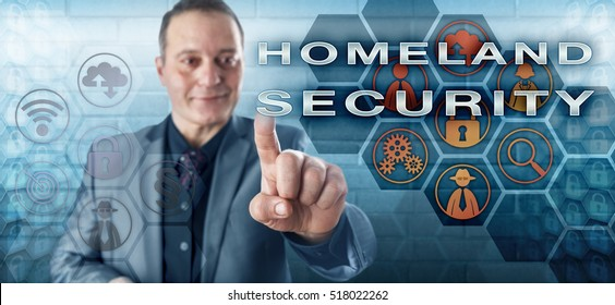 Happy male agent in business suit with toothless smile is activating HOMELAND SECURITY on an interactive control screen. Law enforcement metaphor and security industry concept for homeland defense.