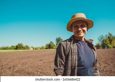 Happy männlich agro Tourist in Hut. Authentisches Porträt ländlicher Bauern. Landarbeiter. Gemüsegarten. Rustikaler Hintergrund. Landsmann. Handarbeit. europäisches Ackerland. Agrotourismus-Konzept. Leerzeichen kopieren