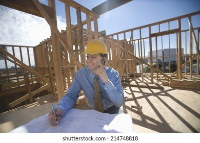 Happy male architect communicating through cell phone with blueprint at construction site