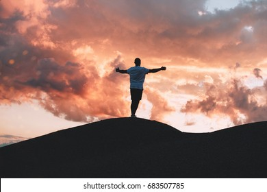 Happy male athlete  with hands up standing on hill at sunset. Healthy lifestyle concept
