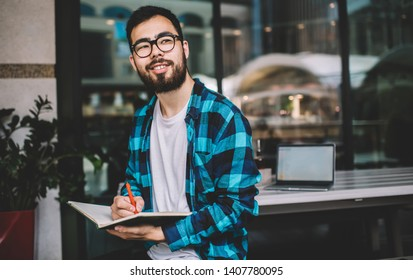 Happy male blogger in optical eyewear for vision correction pondering on idea for university essay, asian hipster student holding textbook for education during time for autodidact in street cafeteria