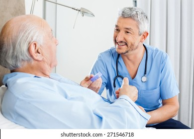 Happy male caretaker discussing prescription medicine with senior man in bedroom at nursing home