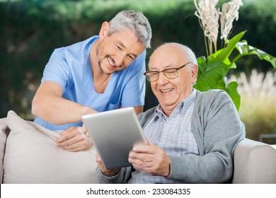 Happy male caretaker and senior man using tablet PC at nursing home porch