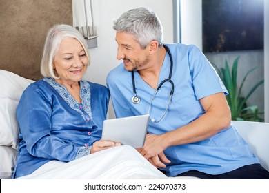 Happy male caretaker with senior woman using digital tablet in bedroom at nursing home