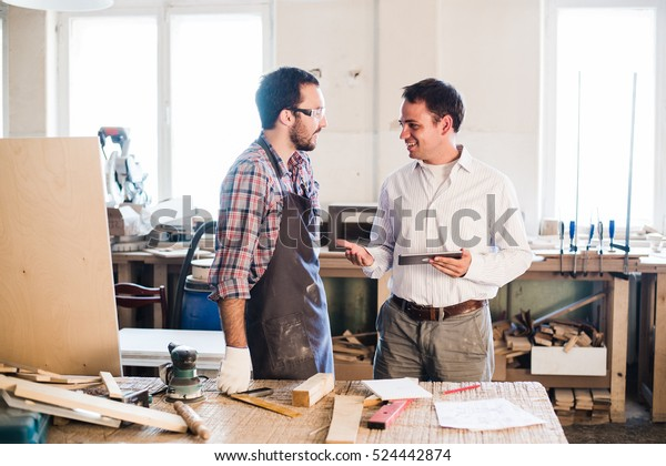 Happy male carpenter showing something to coworker at his notebook papers in workshop