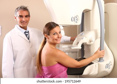 Happy male caucasian doctor assisting a woman patient at mammography machine.