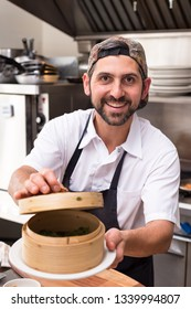 A happy male chef in a restaurant kitchen holding a bamboo dim sum steamer and smiling.