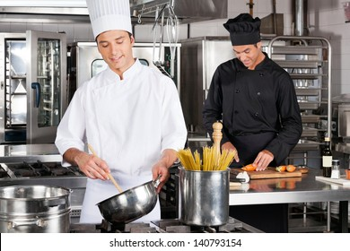 Happy male chefs preparing food in industrial kitchen